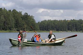 Mannen och tre barn i roddbåten.
