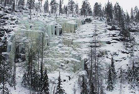A tall and wide uniformly frozen waterfall on the cliff. There is snow and trees in the surroundings.