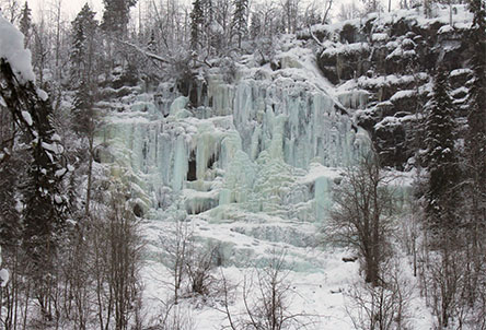A wide and tall frozen waterfall on a tall cliff. There are trees on top of the cliff, trees can also be seen in the snow in front of the cliff.