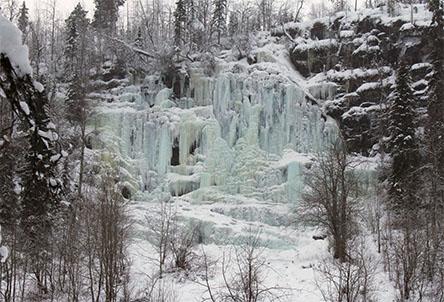 Ett brett och högt fruset vattenfall på en hög klippa. Ovanpå klippan växer träd och även framför kan träd ses i snön.