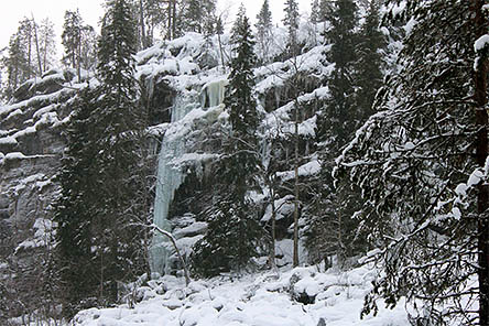 På den låga klippväggen finns ett smalt fruset vattenfall. Det finns träd i omgivningen och i förgrunden finns snötäckta stenar.