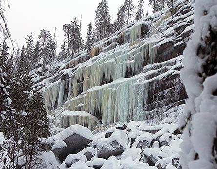 Sektioner av korta frusna vattenfall på klippan, träd växer på klippan och nere i dalen finns stenar som är täckta av snö.