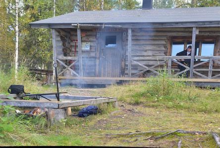 Från eldplatsen utanför vildmarksstugan stiger rök. En vandrare sitter på verandan och tittar mot brasan.