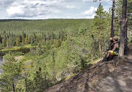 Två vandrare sitter på en hög älvbrink och tittar ut över älven.