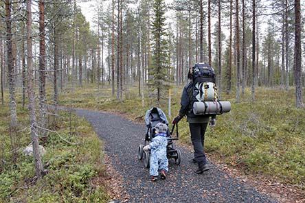 En person går med en banvagn längs en grusstig. Barnet går bredvid och håller tag i vagnen.