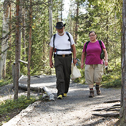 Two hikers walking towards the photographer along a gravel path through the forest.