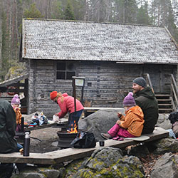 A family having a break at a rest stop. An old log building can be seen in the background.