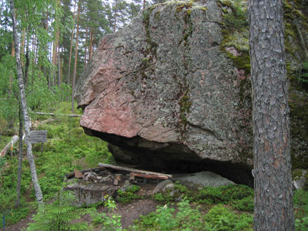 Ett stort flyttblock i tallskogen. Ett överhäng kan ses i flyttblocket och under överhänget finns en eldplats.