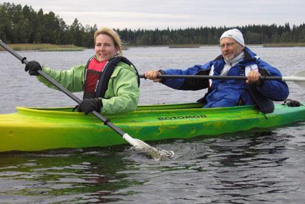 Kaksi retkeilijää melomassa samassa kanootissa. Taustalla vastarannalla metsää.