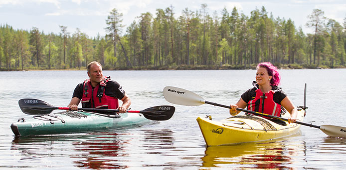 Two kayakers on a lake. In the background you can see the shoreline and a forest.