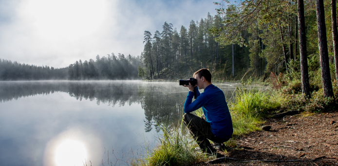 A photographer is taking a picture of a hazy lake. The sun is shining and is creating a mirror image on the lake's suraface.