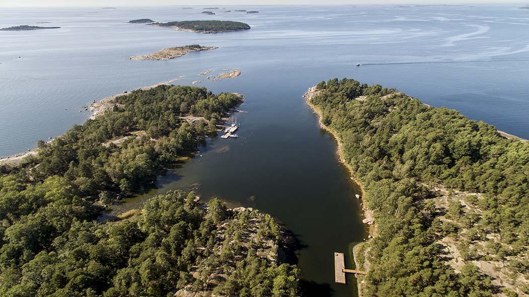 Flygfoto över en ö. Ön bildar en vik och inuti ligger en skyddad båthamn.