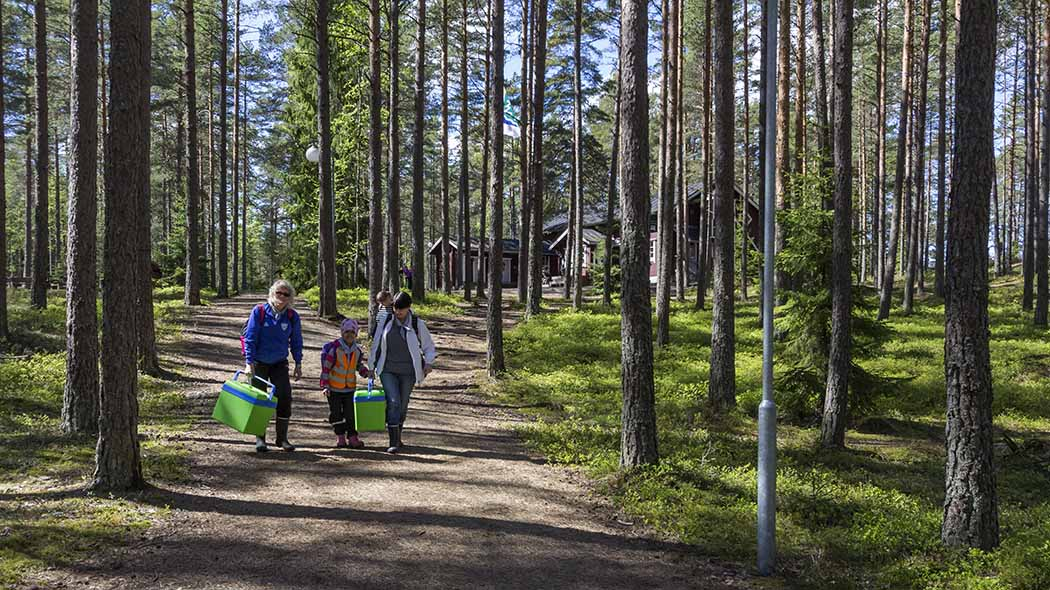 A family with two coolers in their hands are walking along a path towards the photographer. They are surrounded by a coniferous forest. On top of the slope is a red two-story house.