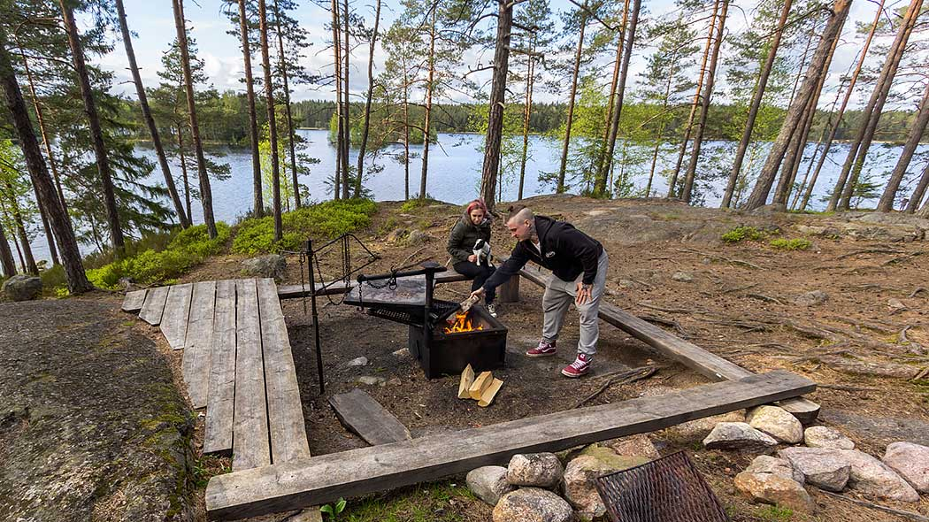 Two hikers are lighting a fire at a fireplace. They are surrounded by sparsely grown forest and a lake landscape opens up in the background.