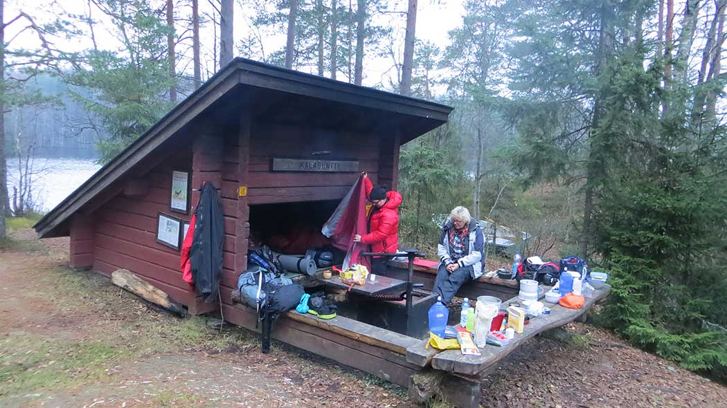A hiker sitting on a bench outside a lean-to shelter in front of a campfire next to another hiker covered in a rescue blanket. Their camp food is spread out on the benches surrounding the fire pit and their sleeping gear is inside the lean-to shelter.