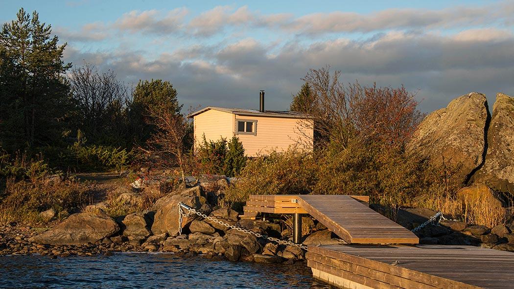 En liten fiskarstuga i kvällssolen. I förgrunden finns en brygga och en stenig strand, i bakgrunden finns träd.