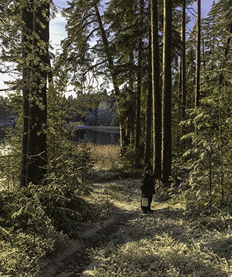 A boy on a forest path carrying a water jug. Sea in the background.