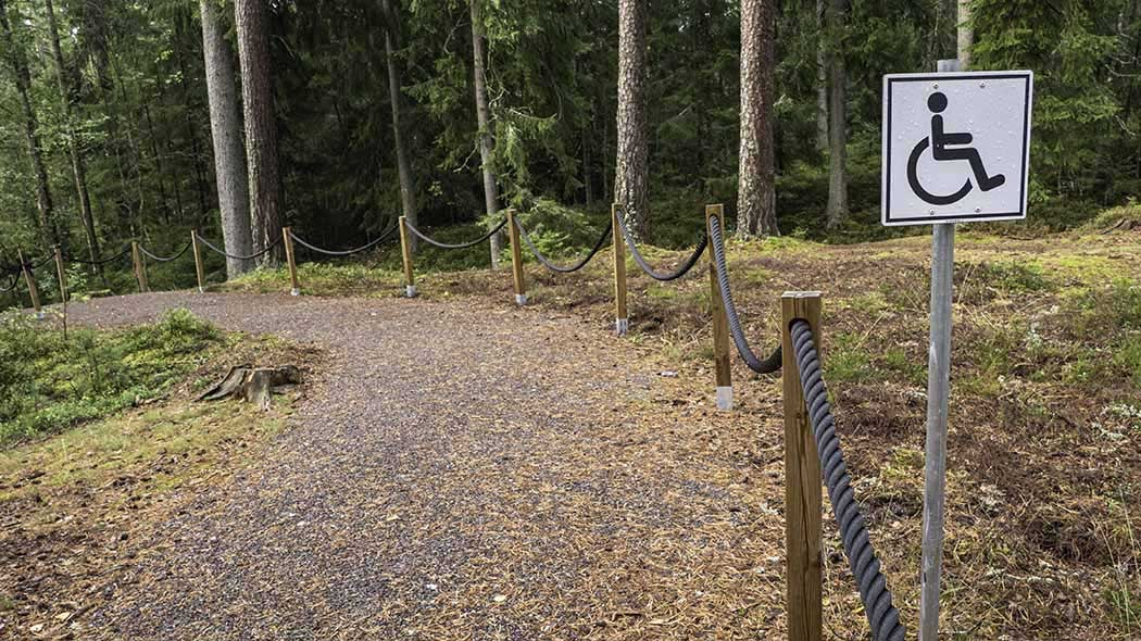 A wide and even path through the forest, one side of the path has a rope handrail. Next to the path is a sign with an image describing that the trail is accessible for persons with disabilities.