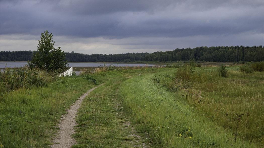 En stig löper invid sjön. Vid stranden är en roddbåt uppdragen och i bakgrunden finns det skog.