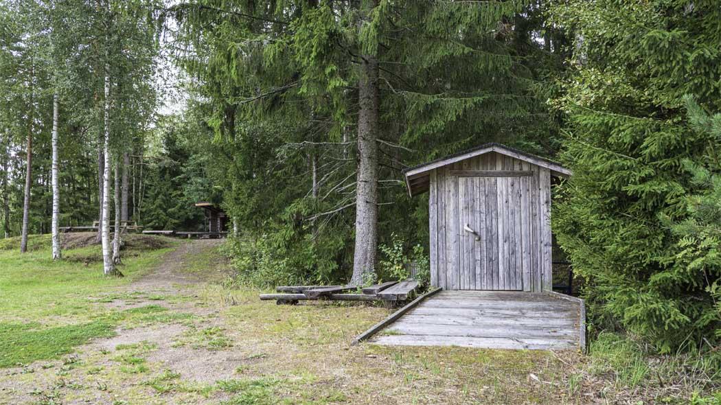 Vid skogsbrynet finns en torrtoalett byggd i trä.