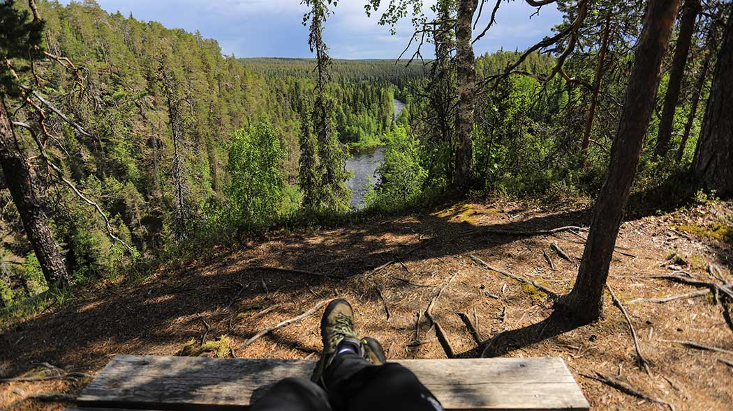 A hiker sitting with his feet on a bench. A view of Oulanka canyon opens up in front.
