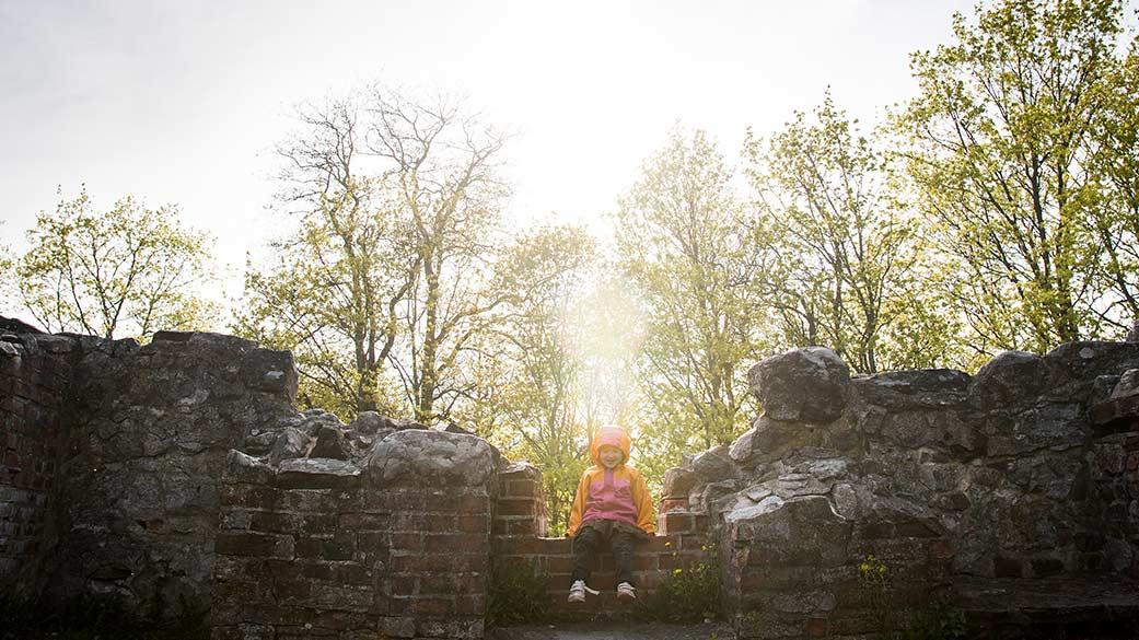 Det sitter ett barn på lägsta platsen av ruinen. I bakgrunden skiner solen på de vårskira lövträden.