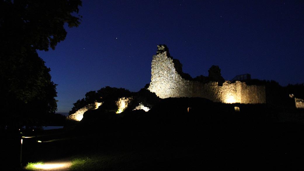 Borgruinerna upplysta under natten. På himlen glimmar några stjärnor.