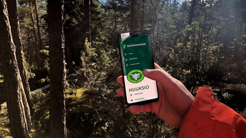 Käsi pitelee kännykkää, jonka näytöllä on Retkikompassi.fi. Taustalla on metsää.