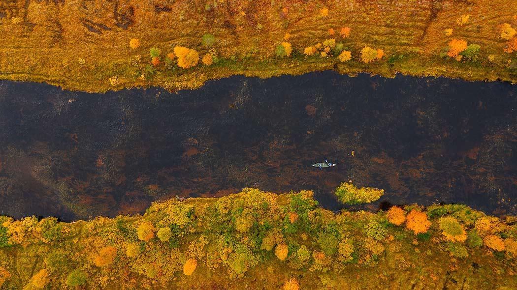 Flygbild av paddlare på ån, på stranden höstens färger.